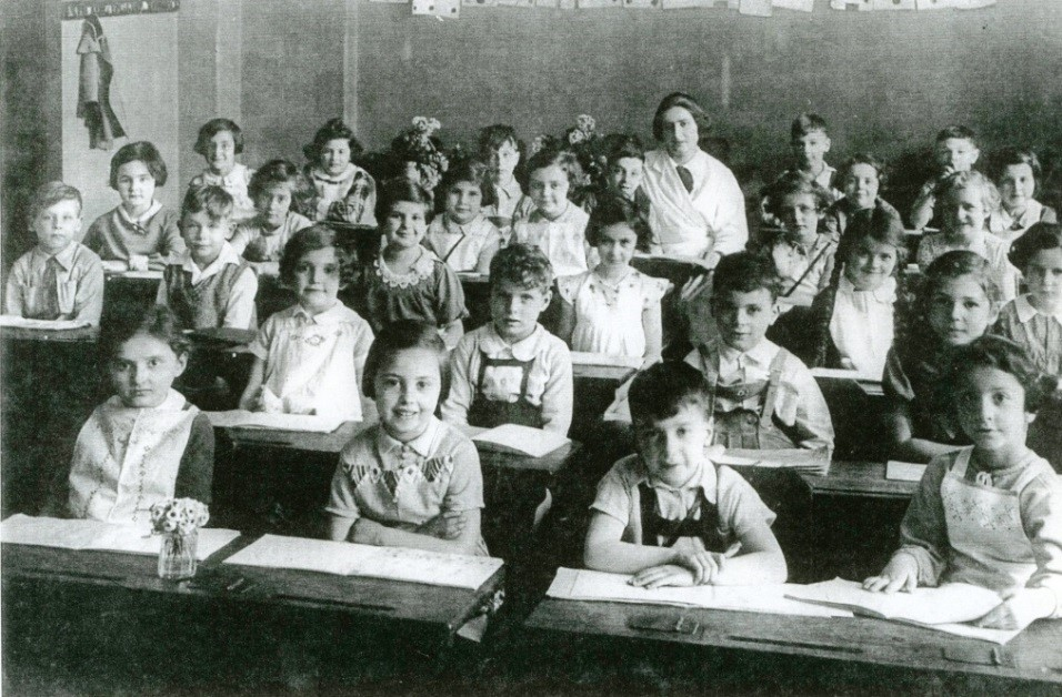 1936 – Carlebach Jewish Day School, first Grade, Leipzig. I sit in the front row far right with my ubiquitous embroidered apron. My friend Helga is the seond from left.