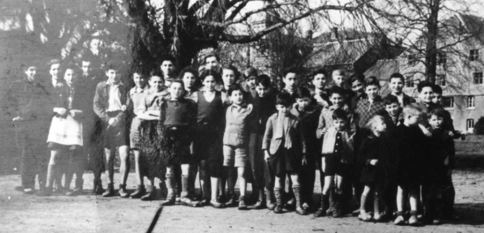 1944 – We were over 60 Jewish children at one time. I am the only girl with my fancy apron. Rosalie and Isabelle were working that morning. Other boys are missing in this picture. The smaller boys had the worst time, they were too young to be able to read their parents letters