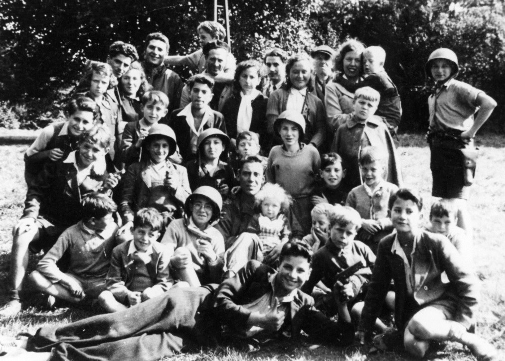 1944 – Several of the boys are wearing American army helmets. One Jewish G.I. is sitting in the center of our group holding a little girl. I am standing two rows behind him
