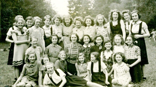 1942 - Sixth Grade at l'Ecole Alfred Mabile, a girls' school. Our teacher is sitting in the center with me at her right. The girls from the local orphanage wear dark skirts with suspenders.